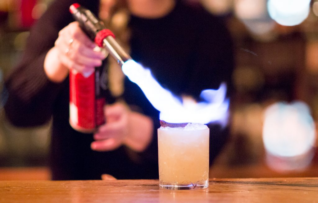 Hands holding a blow torch with a flame igniting a cocktail