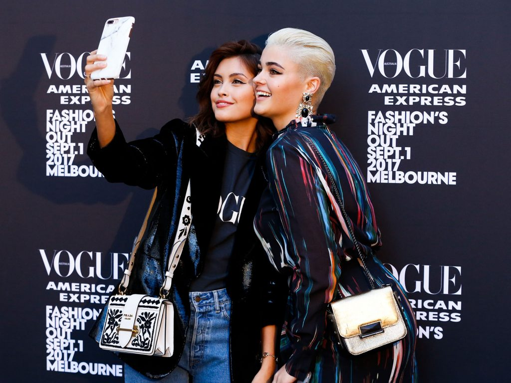 Two girls posing in front of a 'Vogue' media wall, holding a phone out in front of them to take a photo