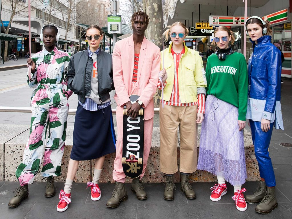 A group of models in various quirky outfits stand in a row on Bourke Street
