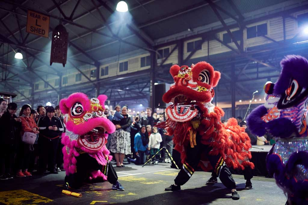 Three Chinese dragon performers in front of a crowd inside a large shed