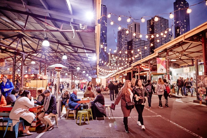 An outdoor market, people sitting on chairs beneath hanging lights.