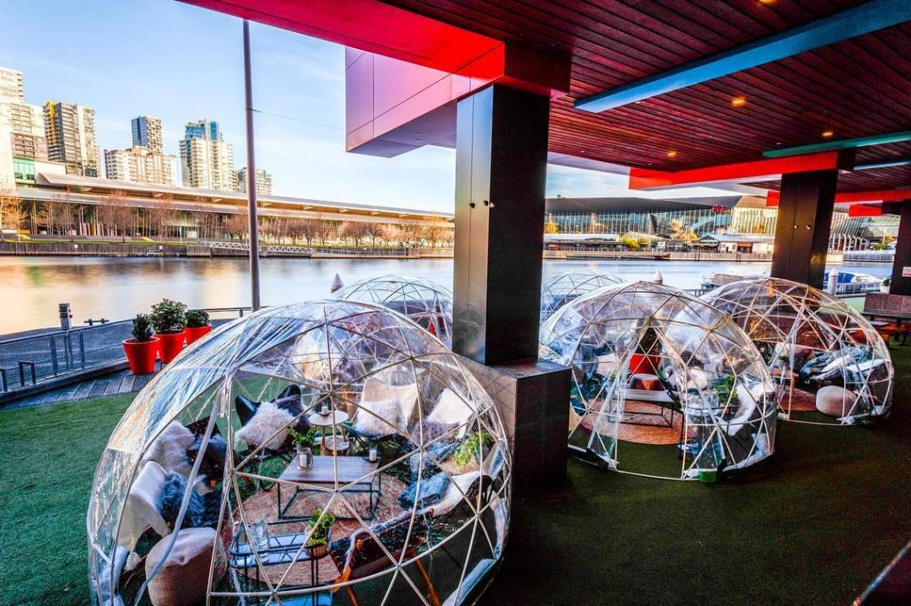 An outdoor beer garden with two clear imitation igloos. People are inside the igloos.