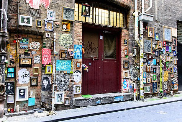 A brick building with a wooden door which is surrounded by street art