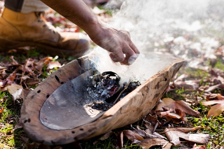 Hands preparing a fire on a small wooden tray in an outdoor park