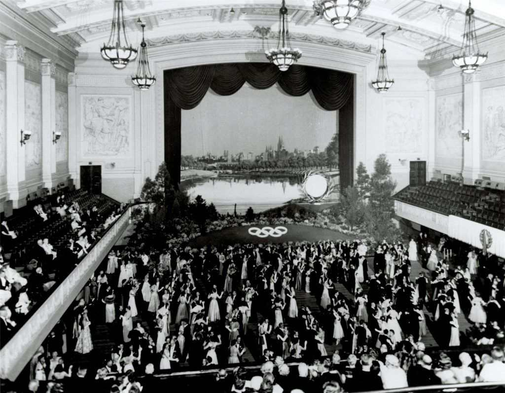 A black and white photo of an old town hall with people dancing