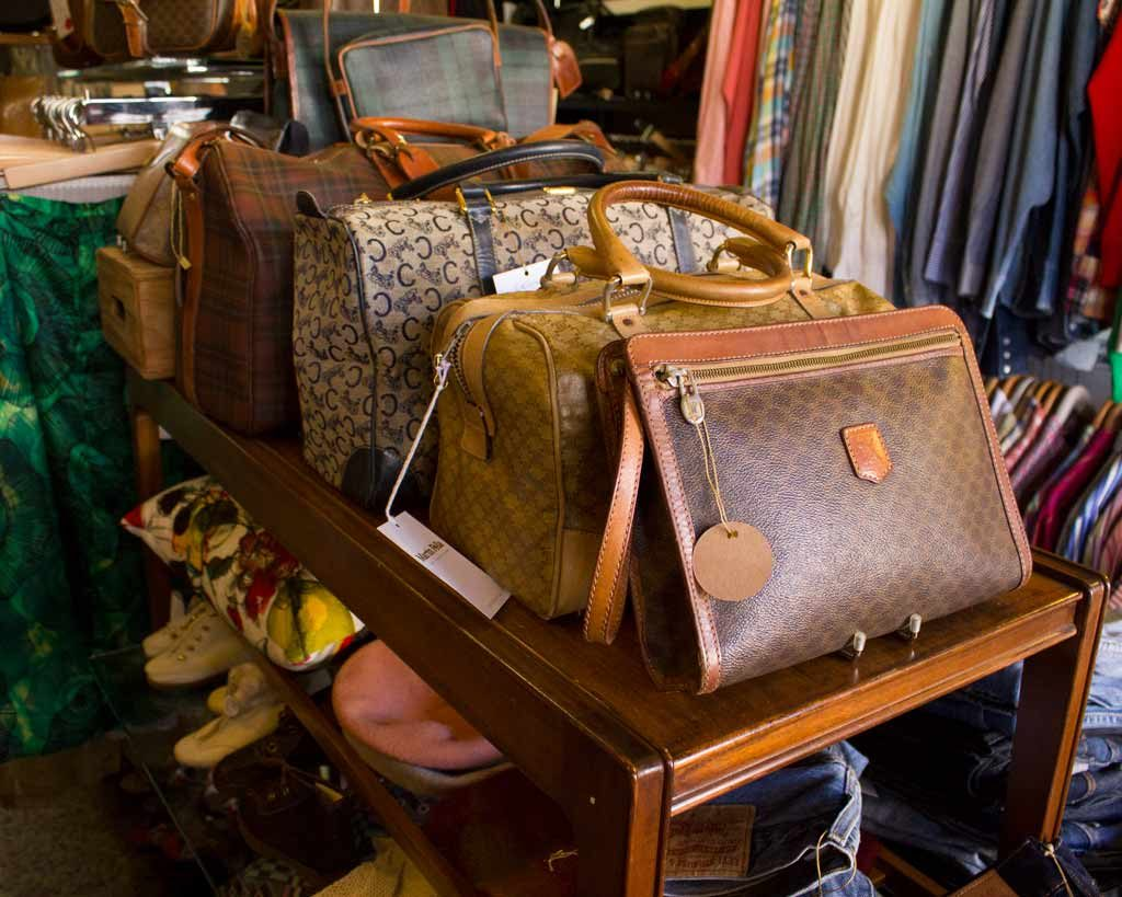 Vintage brown leather bags on a wooden shelf in a vintage store