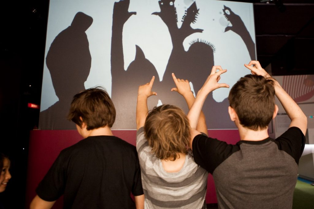 Three kids making shadows in front of a white screen
