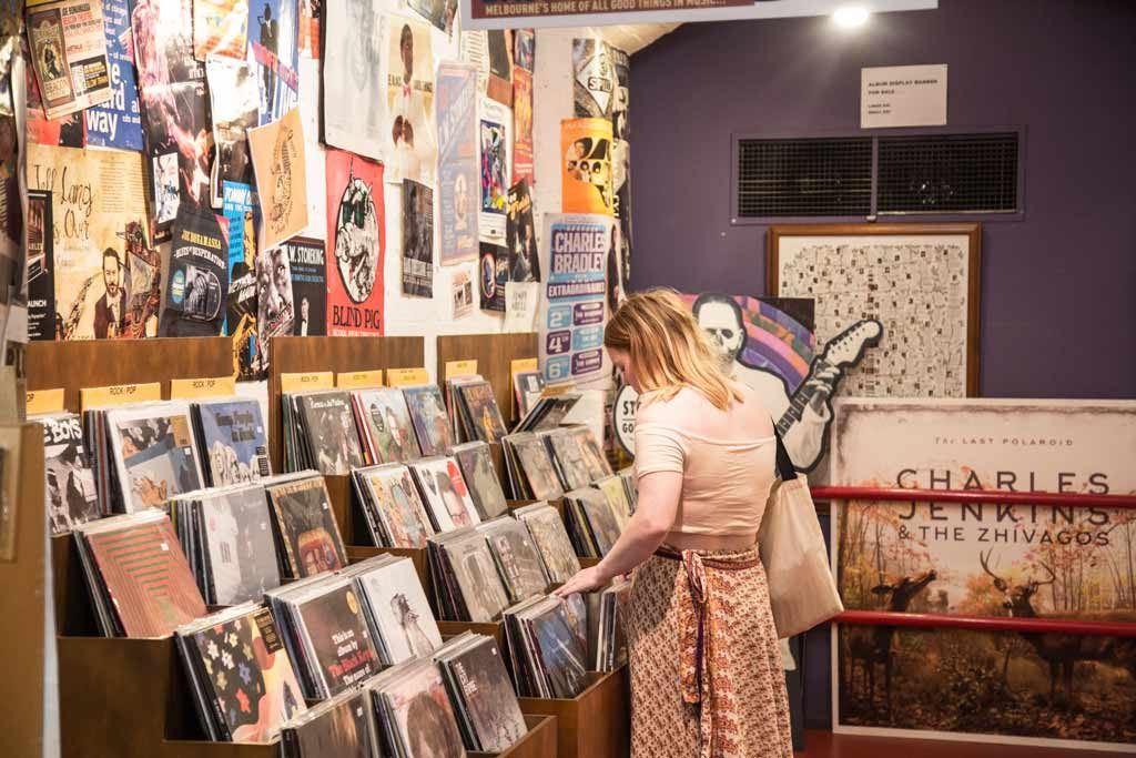 A woman in a vintage skirt and top browsing through a record shop
