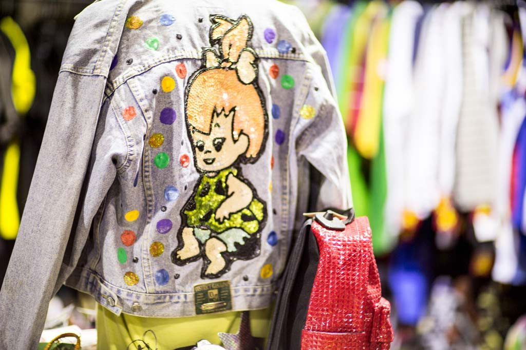 A denim jacket with a cartoon character embroidered on the back on display at a vintage store