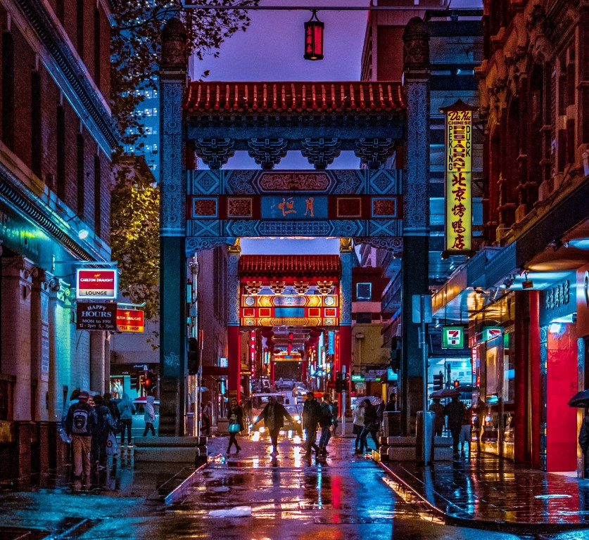A busy city street at night with a Chinese ornamental arch and lots of neon signs with Chinese lettering