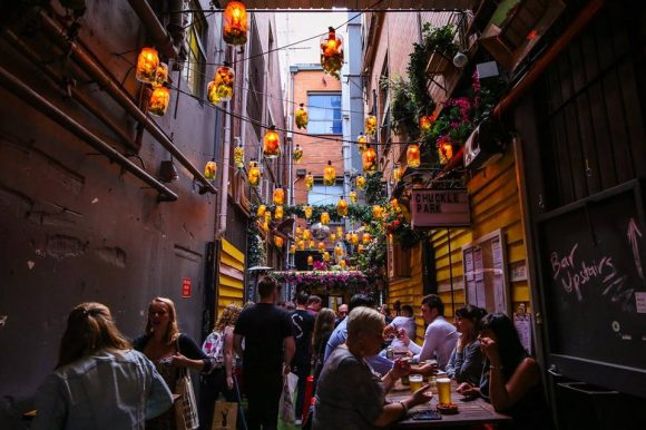 People sitting and drinking at atables under lanterns in a tiny laneway
