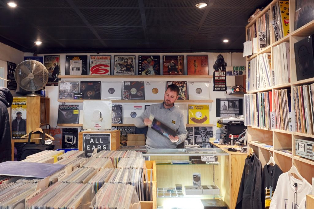 A man taking a vinyl record out of its sleeve surrounded by racks and wall displays of records