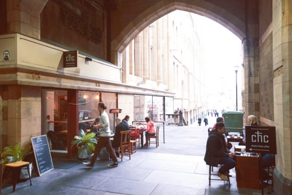 People sitting in a cafe under a cathedral arch