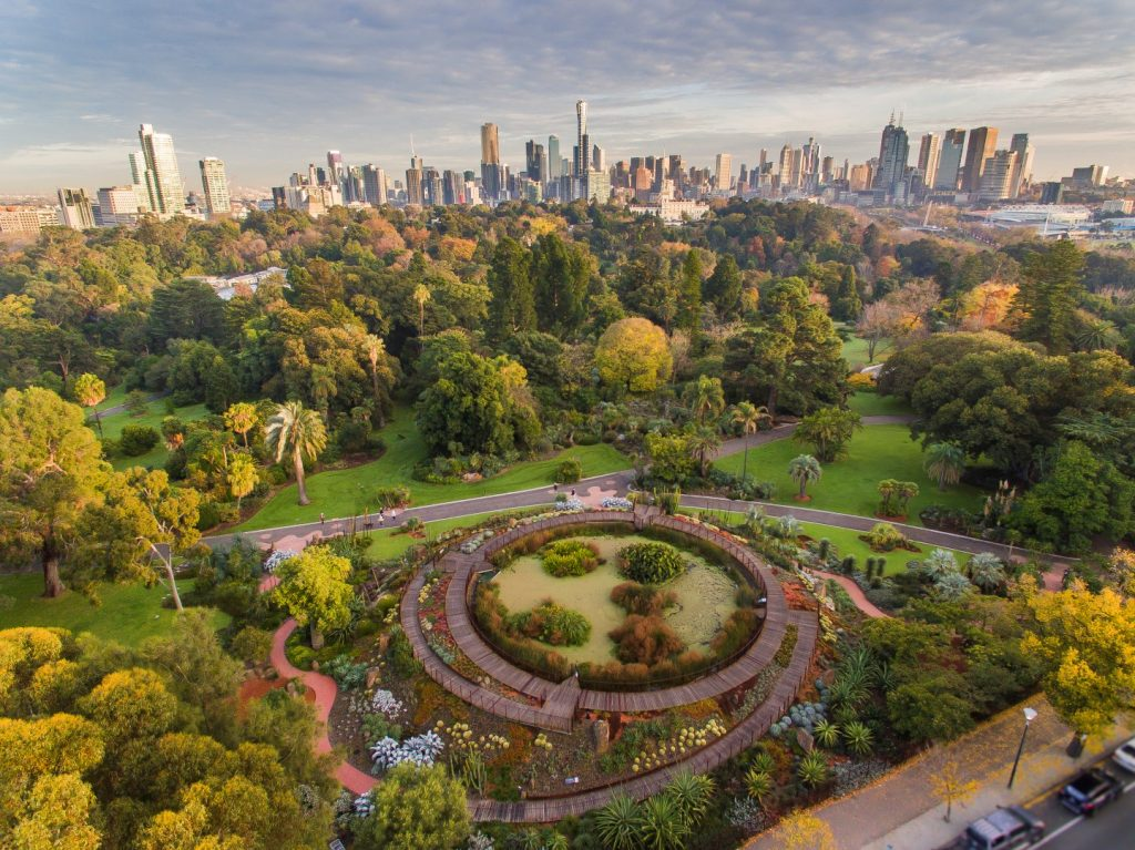 Aerial view of a very intricate garden with the city skyline in the background