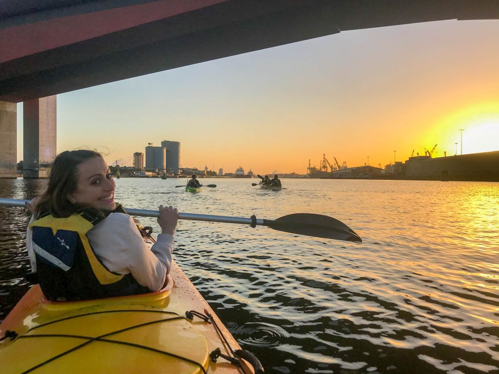 A young woman in a kayak on a river smiling with the sunset in background