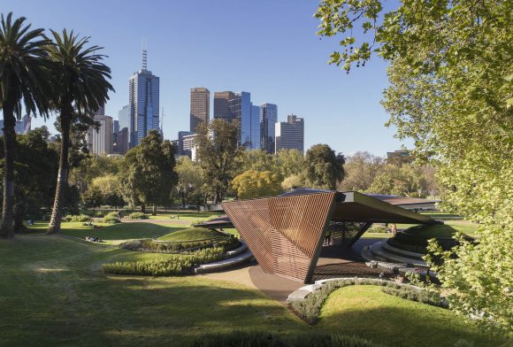 A modern looking shelter structure in an outdoor park, with the city skyline in the background