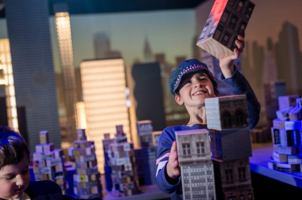 a child building a mini skyscraper in a gallery