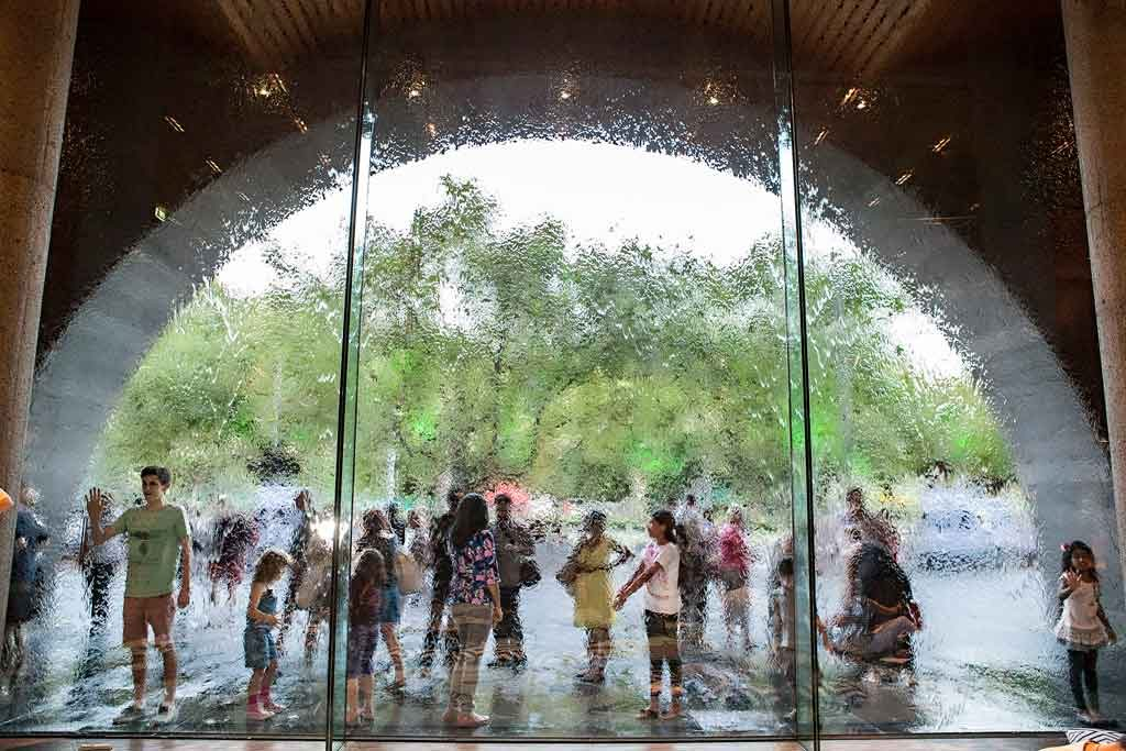 A group of children standing by a semi-circle shaped window with a water feature running down it
