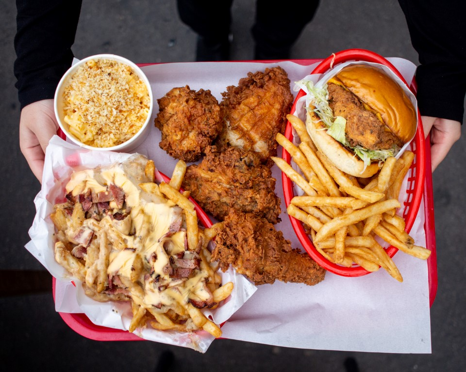 Bird's eye view of a tray with fried chicken, loaded fries and burgers on it
