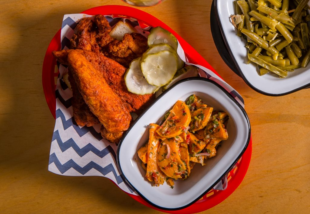 An aerial shot of a red tray with blue and striped paper. Fried chicken, pickles and slaw are on top.