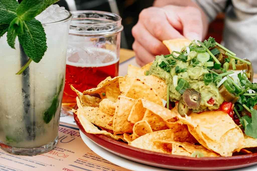 Nachos on a plate with a margarita beside it