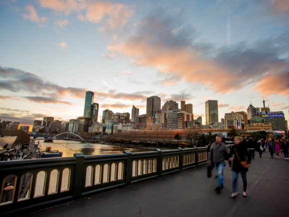 People walking over a bridge over a river at sunset with the city skyline in the background