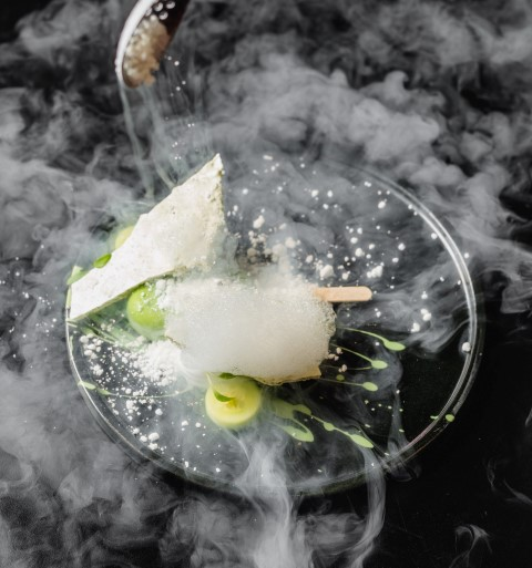 A plate with fairy floss, meringue, fruit and covered in smoke