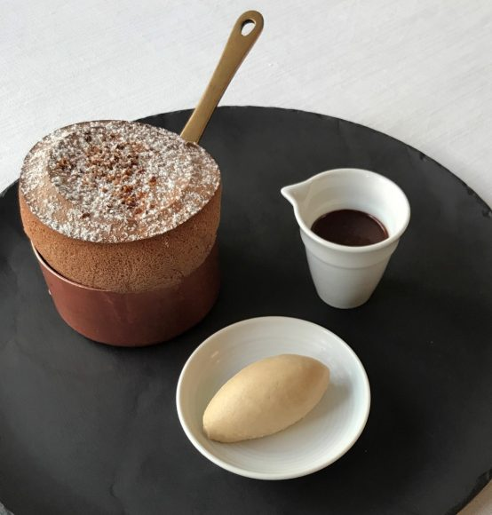 A souffle dessert with a small jug of chocolate sauce and a small bowl of ice cream