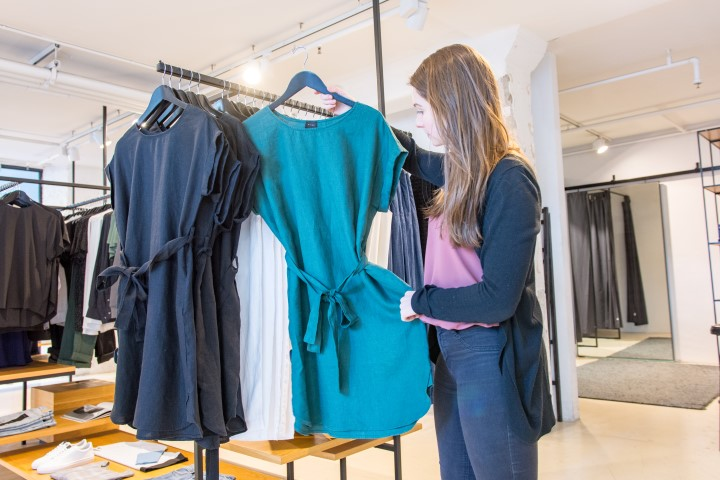 A girl holds out a dress on the racks at a womens clothes store