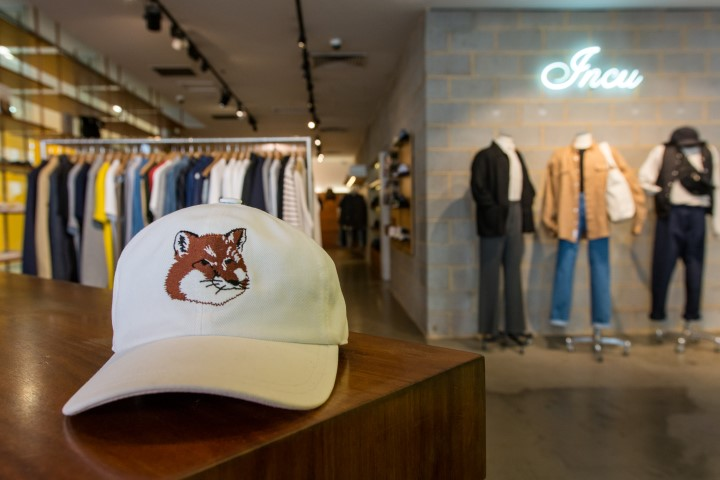 A cap with a picture of a fox on it, with clothes racks and mannequins modelling men's clothes in the background