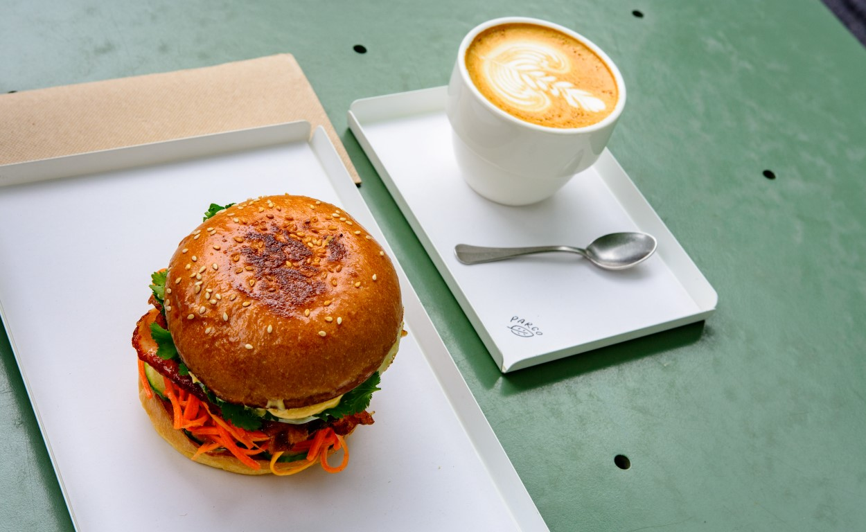 A burger on a white plate with a coffee beside it
