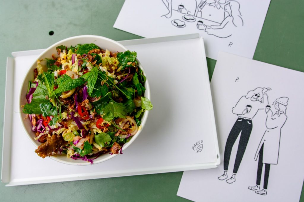 A salad on a white plate with drawings underneath it