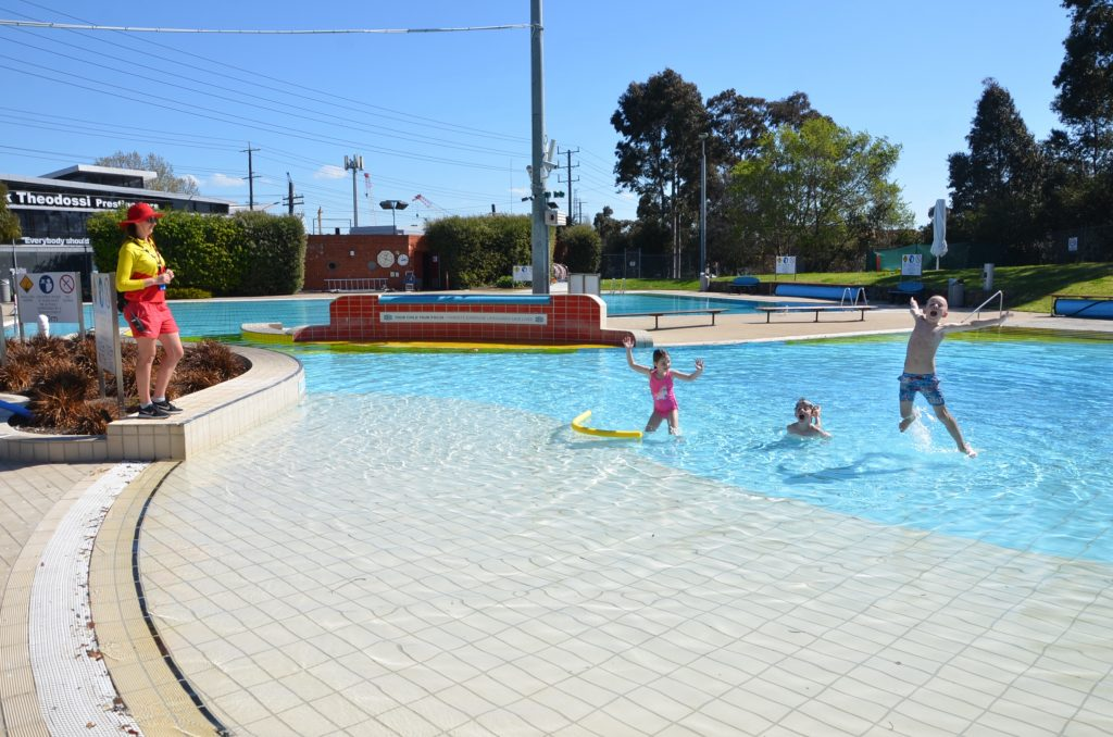 Three children splashing in an outdoor pool with a lifeguard watching