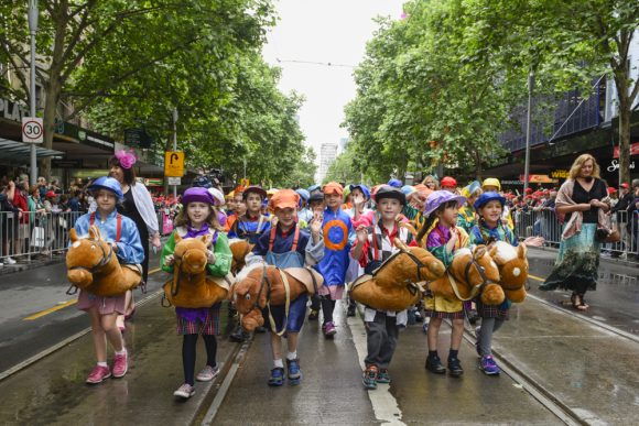 A group of kids dressed up like jockeys walking in a big street parade
