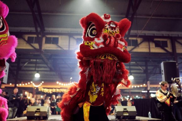 A Chinese lion dancing at a market