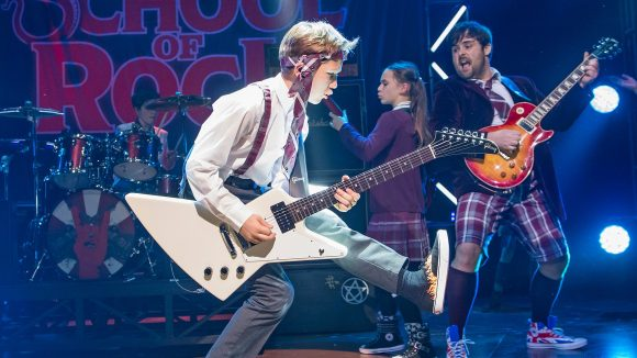 A group of teenagers dressed in high school uniforms performing in a rock band