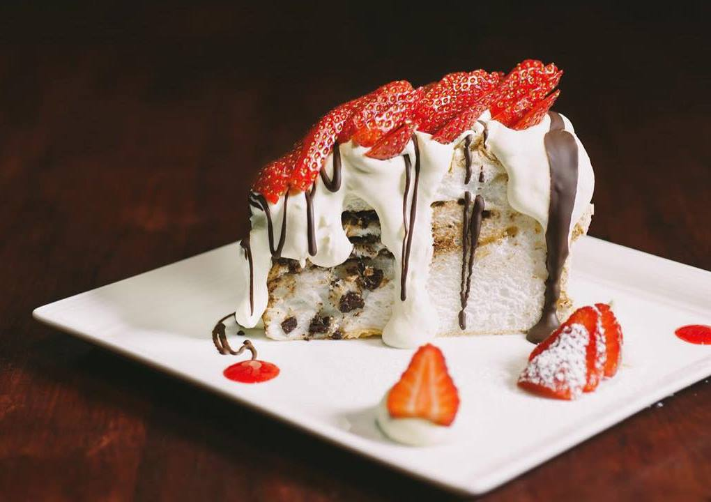 A slice of pavlova covered in cream, strawberries and chocolate sauce