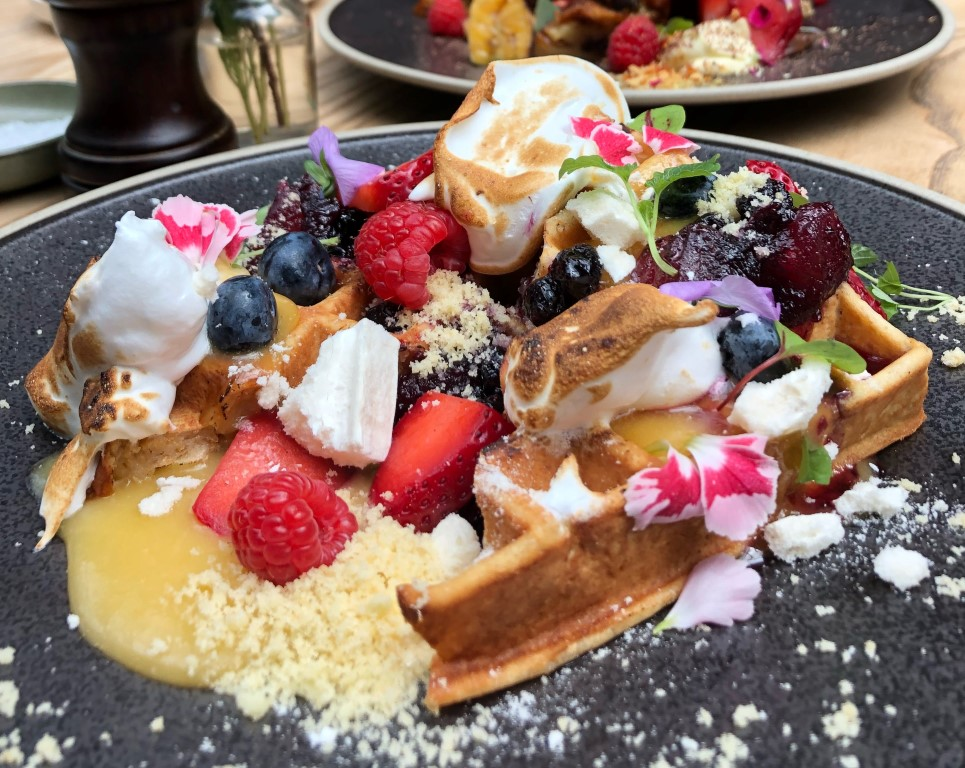 A waffle covered in syrup, merigue pieces, berries and edible flowers