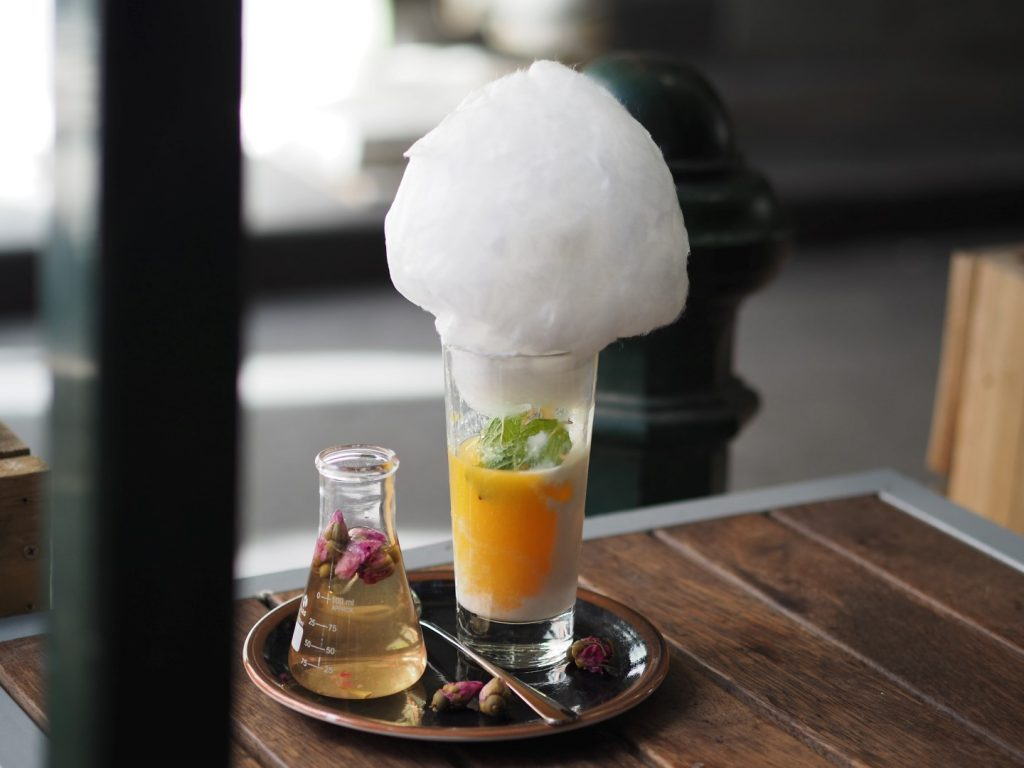 A small glass bottle next to a large glass cup with fairy floss on top of it
