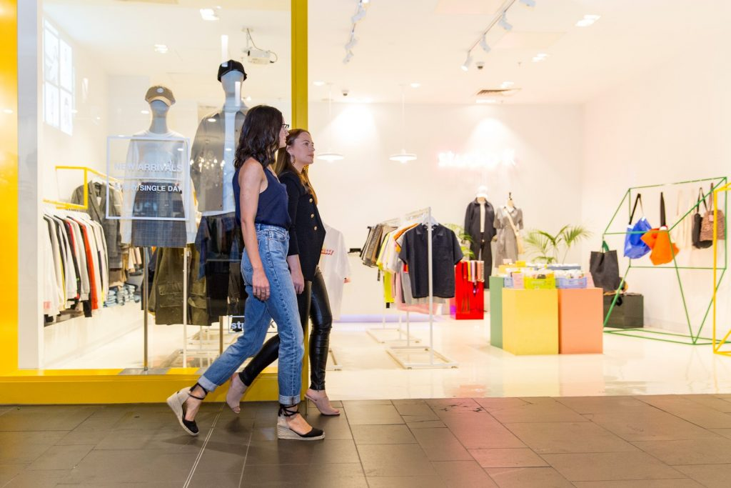 Two women walking in front of a minimalist style shop