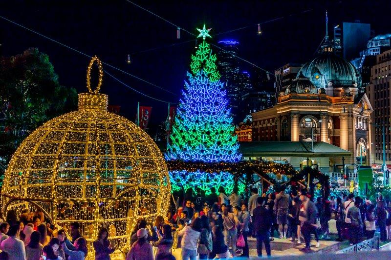 A group of people looking at twinkling Christmas tree and giant bauble made from Christmas lights