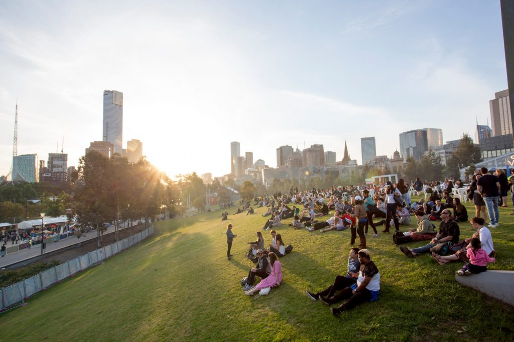 A crowd of people sitting on a grassy hill with the sun setting and skyscrapers in the background