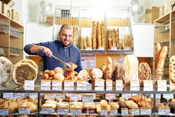 A man at a bakery stall surrounded by cakes and pastries, using tongs to pick up a croissant