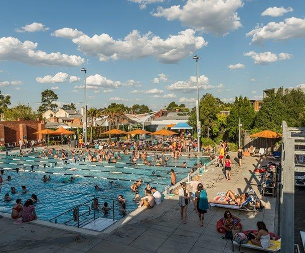 picture of large public pool with many people swimming