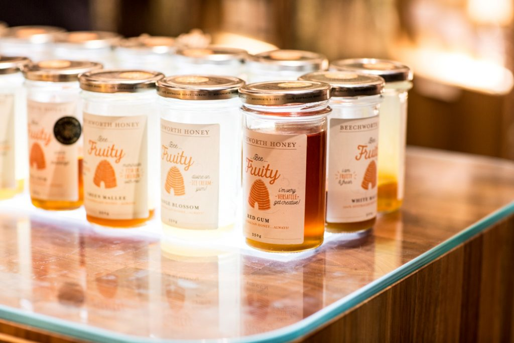 Various jars of honey on a wooden bench