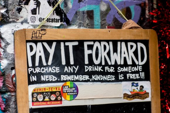 A blackboard hanging on a street art covered wall with the words Pay it forward written on it