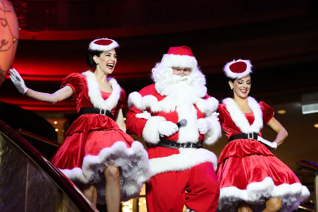 Santa Claus linking arms with two women dressed in red Christmas dresses