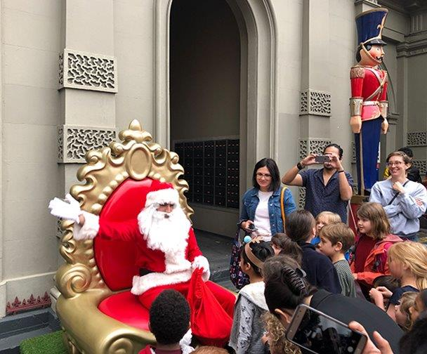 Santa sits on his throne with crowds of people surrounding him