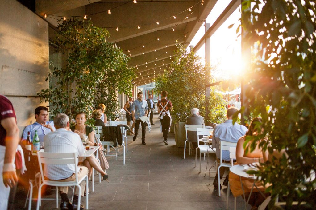 People sitting at outdoor tables under grapevines in a restaurant at sunset