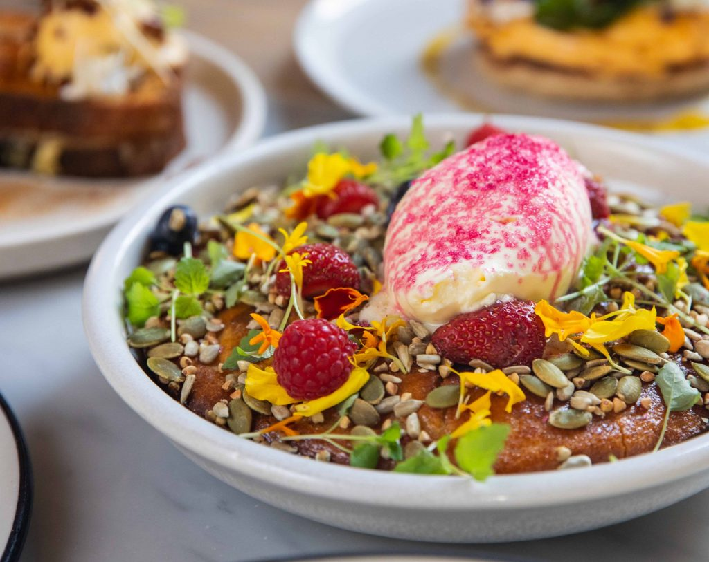 A table at a cafe with bowls of breakfast food on it, a bowl in the foreground filled with a large pancake and topped with edible flowers and ice cream